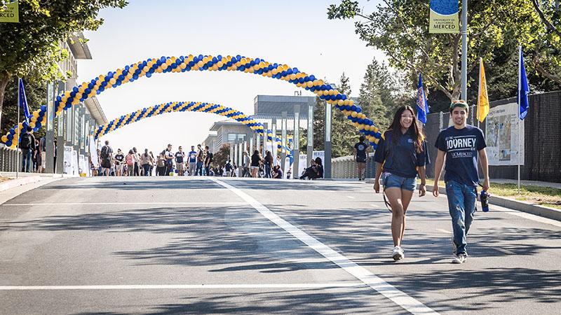 students walking across uc merced campus bridge